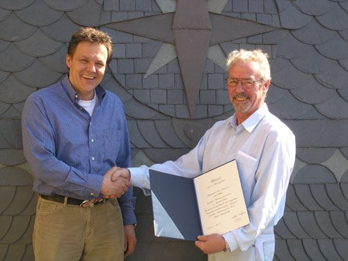 Herr Kadow gratuliert seinem Dachdeckergesellen zum Betriebsjubilaeum